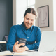 Smiling young male office worker using smartphone while working on laptop in modern office centre - PhotoDune Item for Sale