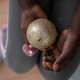 Girl holding shiny golden holiday bauble in her hands - PhotoDune Item for Sale