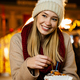 Portrait of happy woman girl eating donuts and enjoying christmas market. Holiday christmas people - PhotoDune Item for Sale