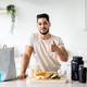 Sporty young Arab guy with wholesome foods and protein shake gesturing thumb up at kitchen - PhotoDune Item for Sale