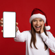 Amazing Offer. Excited Young Lady In Santa Hat Showing Blank Smartphone - PhotoDune Item for Sale