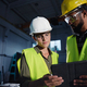Low angle view of industrial inspectors with tablet doing a general check up and talking indoors at - PhotoDune Item for Sale