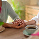 Close up of senior mother holding hand of adult daughter when having coffee together indoors at home - PhotoDune Item for Sale