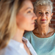 Senior mother looking at her adult daughter indoors at home. Selective focus on woman in background - PhotoDune Item for Sale