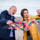 Senior man and his preteen granddaughter preparing kite for flying on sandy beach - PhotoDune Item for Sale