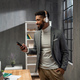 Happy young african american businessman with smartphone and headset working indoors in office - PhotoDune Item for Sale