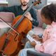 Intercultural girl writing musical notes on paper during cello play lesson - PhotoDune Item for Sale