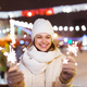 Smiling young woman wearing winter knitted clothes holding sparkler outdoors over snow background - PhotoDune Item for Sale