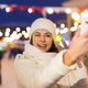 A woman on the rink is skating and taking selfie on smartphone. New Years Eve and Christmas. Fairy - PhotoDune Item for Sale