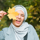 Autumn muslim woman holding maple leaf outdoors in sunny day. Beautiful arab wearing hijab girl in - PhotoDune Item for Sale