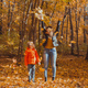 Single parent family playing with autumn leaves in park. Happy mom and son throw autumn leaves up in - PhotoDune Item for Sale