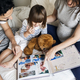 Pregnant family looking through a family photo album - PhotoDune Item for Sale