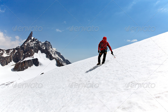 Climber standing on a glacier looking at a mountain peak - Stock Photo - Images