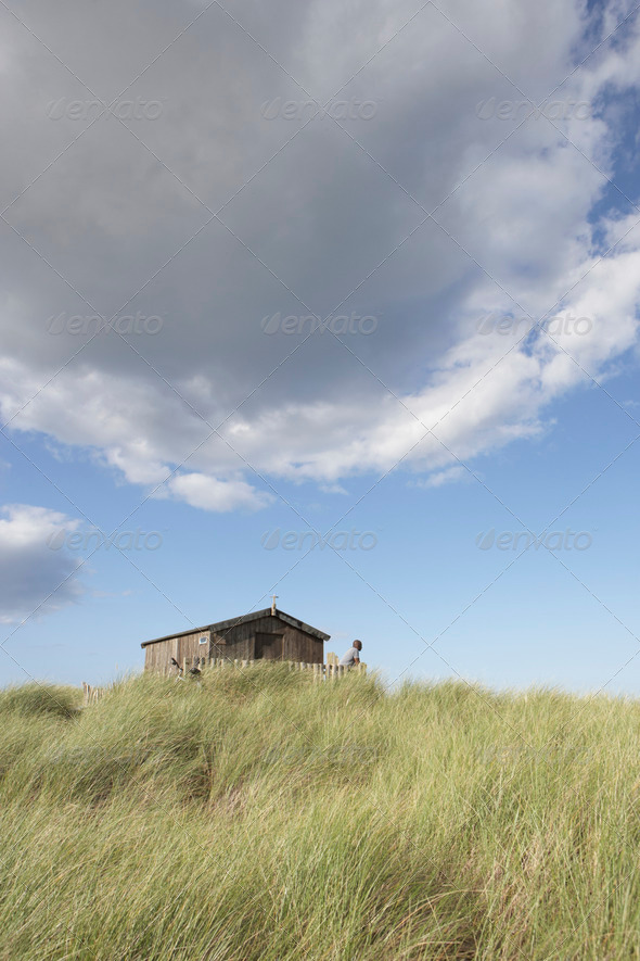 Distant View Of Young Couple Relaxing In Wooden Beach Hut Amongst Dunes - Stock Photo - Images