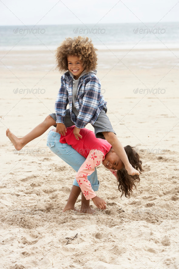 Happy children playing on beach - Stock Photo - Images