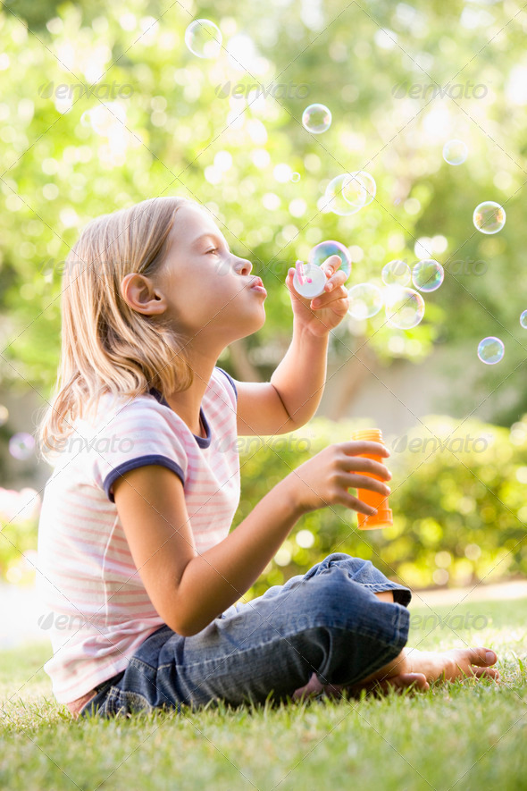 Young girl blowing bubbles outdoors - Stock Photo - Images