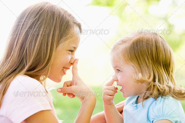 Two sisters playing outdoors and smiling - Stock Photo - Images