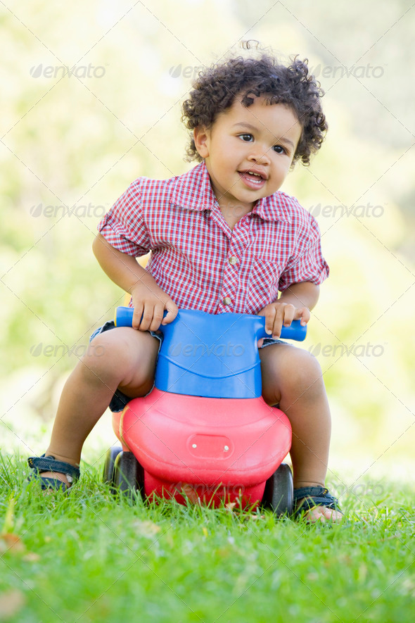 Young boy playing on toy with wheels outdoors - Stock Photo - Images