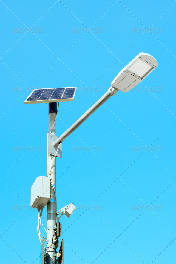 Solar panel powered street light lamp on blue sky background - Stock Photo - Images