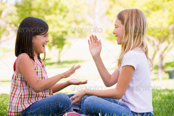 Two young girl friends sitting outdoors playing patty cake smiling - Stock Photo - Images