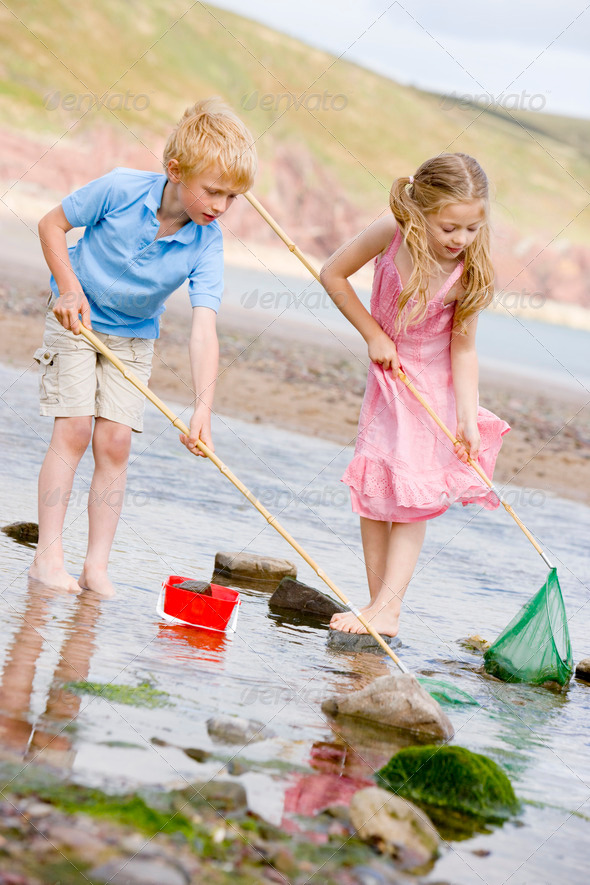 Brother and sister at beach with nets and pail - Stock Photo - Images