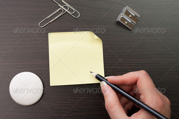 Woman Writing With Pencil On Yellow Sticker - Stock Photo - Images