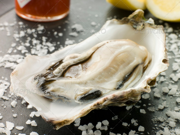 Opened Rock Oyster with Hot Chilli Sauce Lemon and Sea Salt - Stock Photo - Images