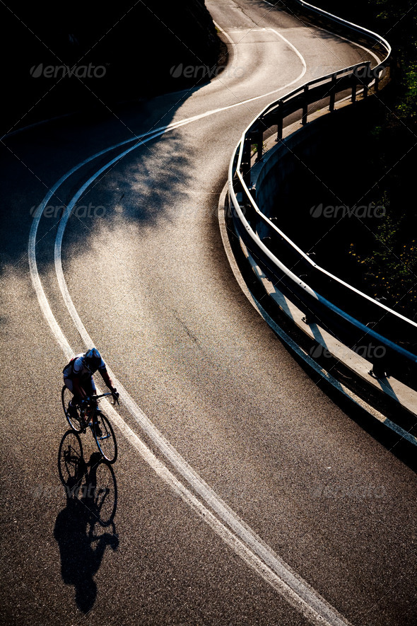 Cyclist riding along a mountain road - Stock Photo - Images