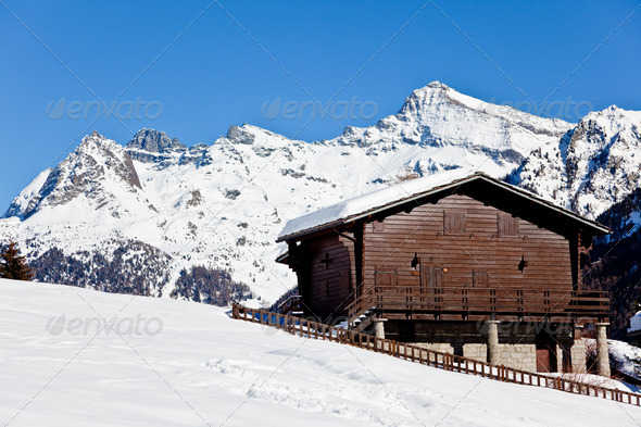 Wooden cottage over snowed mountain - Stock Photo - Images