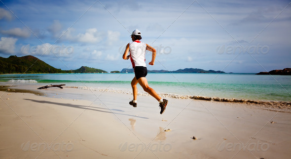 Man running on a tropical beach - Stock Photo - Images