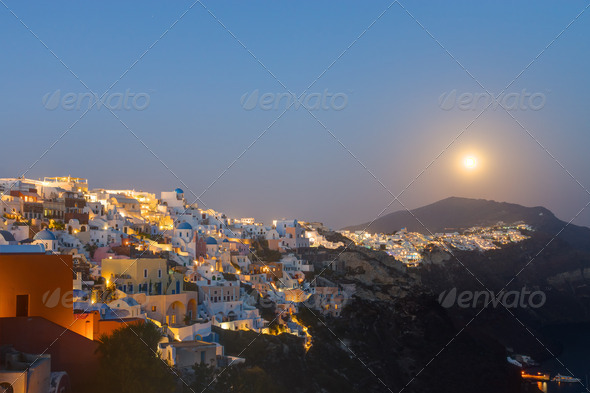 The moon rises over Oia  - Stock Photo - Images