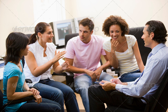 Man giving lecture to four people in computer room - Stock Photo - Images