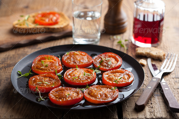 baked tomatoes with herbs and olive oil - Stock Photo - Images