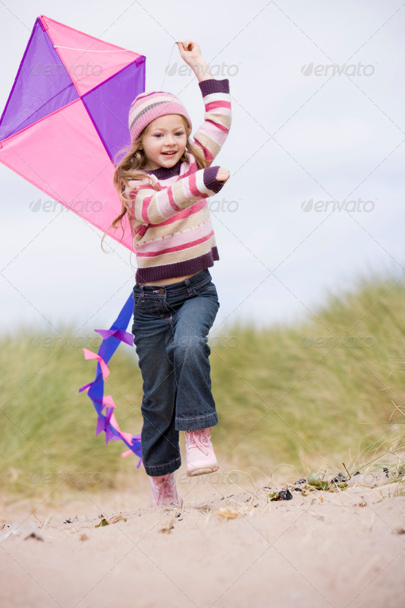 Young girl on beach with kite smiling - Stock Photo - Images