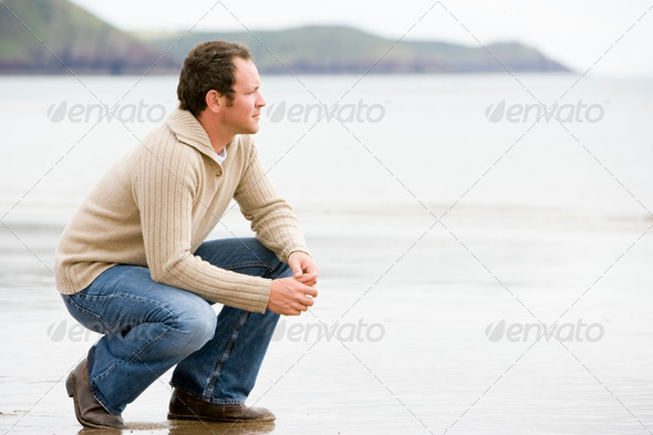 Man crouching on beach - Stock Photo - Images