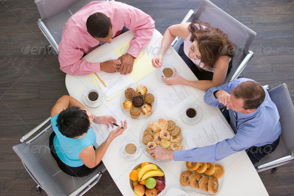 Four businesspeople at boardroom table with breakfast - Stock Photo - Images
