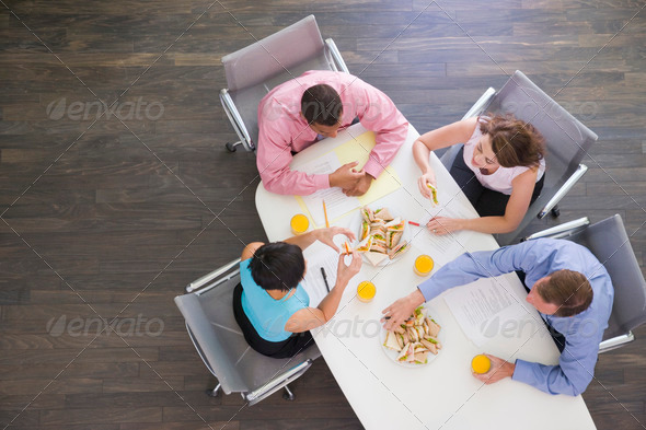Four businesspeople at boardroom table with sandwiches - Stock Photo - Images