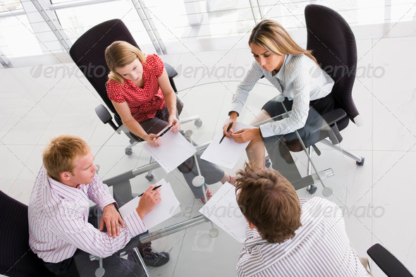 Four businesspeople in a boardroom with paperwork - Stock Photo - Images