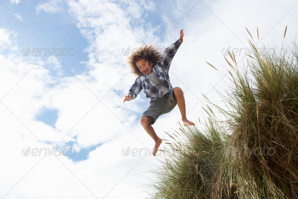 Boy jumping over dune - Stock Photo - Images
