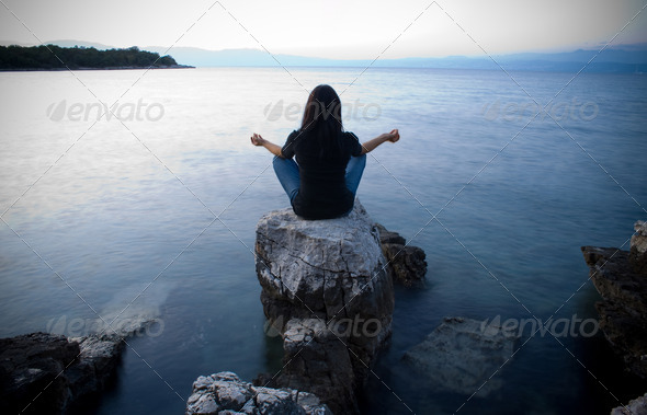 Meditation by the sea at dusk - Stock Photo - Images