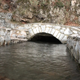 Stream of Water Passes under a Small Stone Bridge - VideoHive Item for Sale