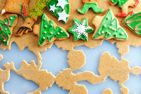 Christmas gingerbread cookies over dough - Stock Photo - Images
