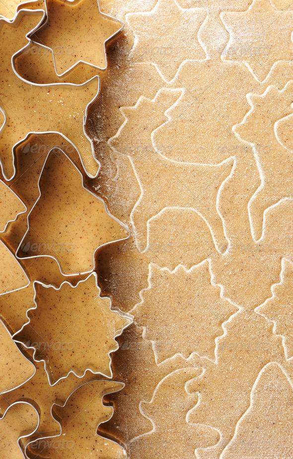 Christmas cookie cutters over gingerbread dough - Stock Photo - Images
