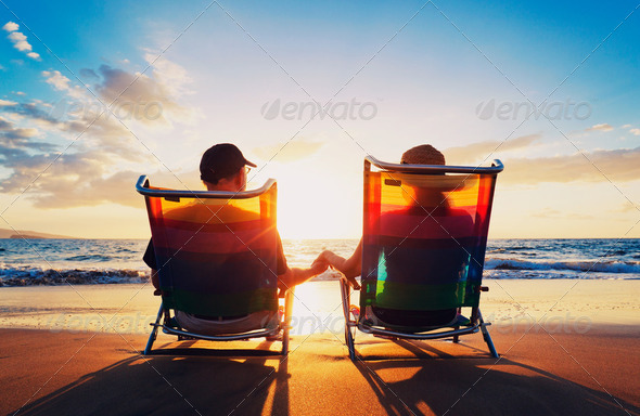 senior couple of old man and woman sitting on the beach watching - Stock Photo - Images