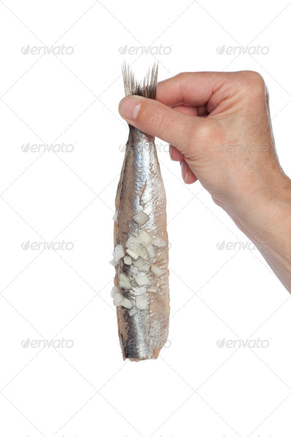 Hand holding a fresh herring with onions - Stock Photo - Images