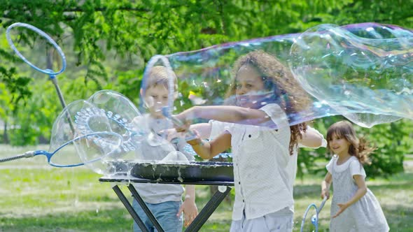 Excited Kids Playing With Soap Bubbles In Park By