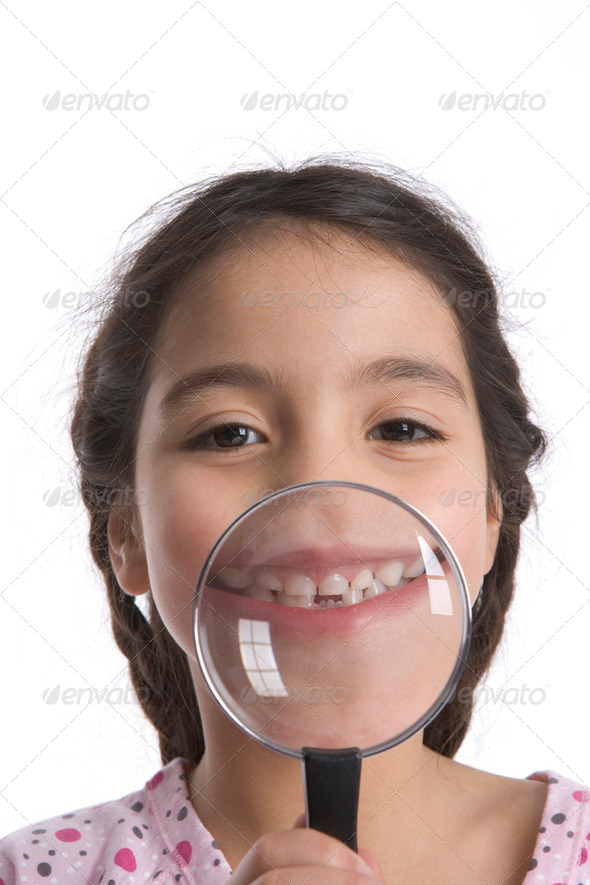 Little Girl Shows Her Teeth Through A Magnifying Glass - Stock Photo - Images