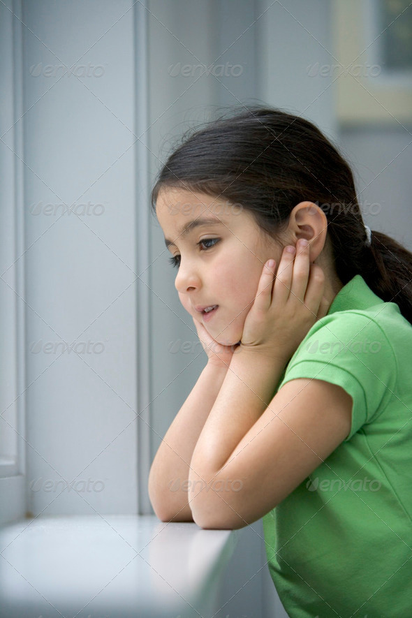 Little girl is looking out of the window with a sad face - Stock Photo - Images