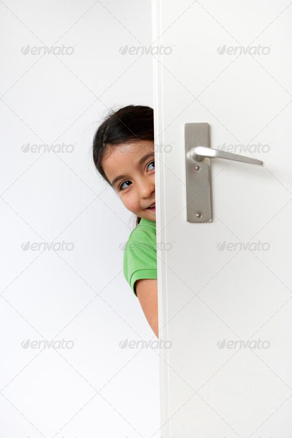 Little girl is hiding behind the door - Stock Photo - Images
