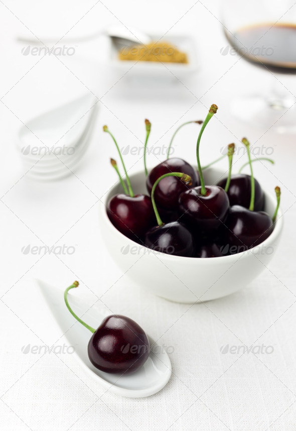 Cherries on white spoon and bowl, sherry glass brown,sugar - Stock Photo - Images